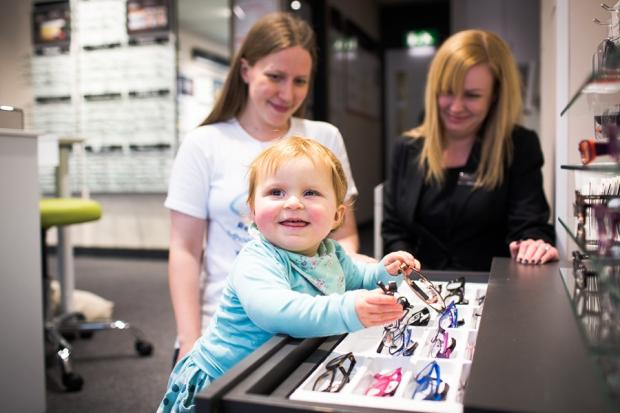 Eye cancer sufferer Eliza Deakin with mum Lucy and store manager Gemma Exley at the new Vision Express branch
