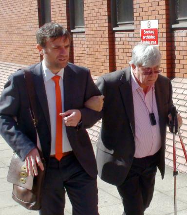 Sir David Jones is helped into court today by his son Stuart