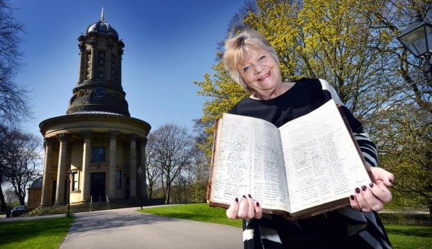 Valerie Jenkins, church secretary, holds a book which dates back to the very early 1900s