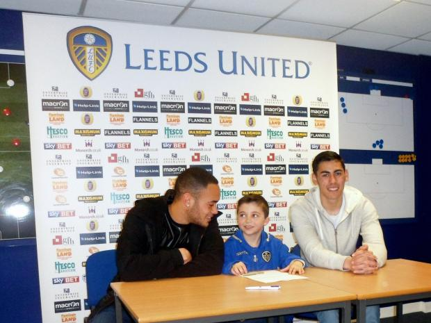 Sami is pictured signing his contract with Leeds United's Lewis Walters (left) and Eric Grimes,