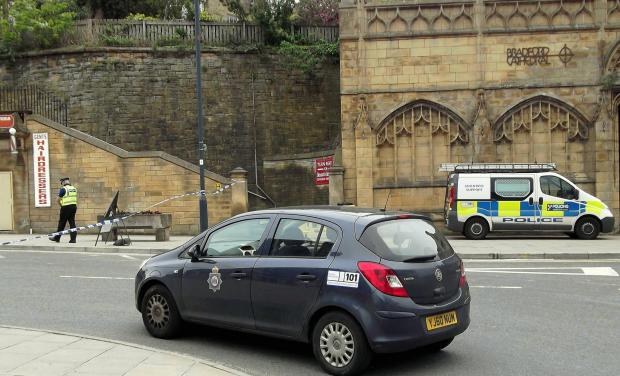 CORDENED OFF: Police officer and a police car at the scene of the incident in Bradford