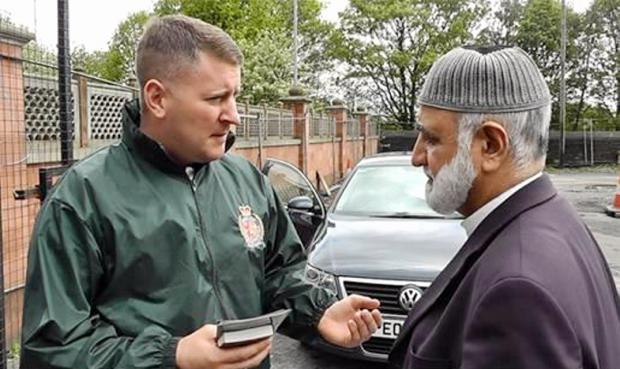 A Britain First member hands out leaflets during action which is thought to have targeted ten mosques