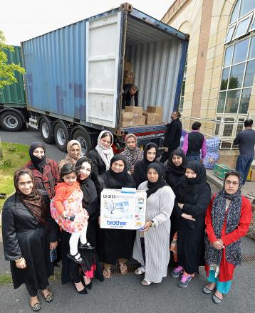 On ITS WAY: Razia Amini and other volunteers (right) help pack a shipping container to take donations to a remote area of Gambia