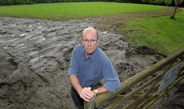 Councillor Martin Love in front of the churned-up field
