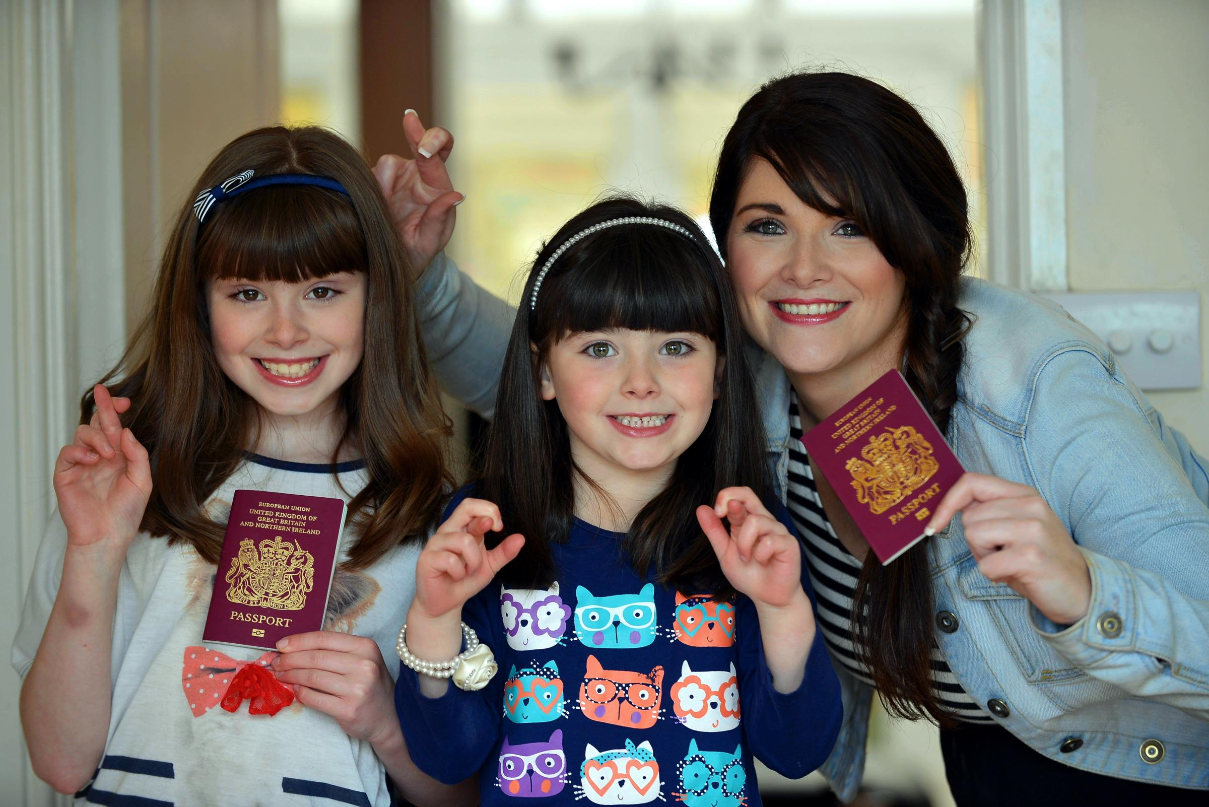 Mum Rachael Delaney with Keira (left) and Zara and their passports