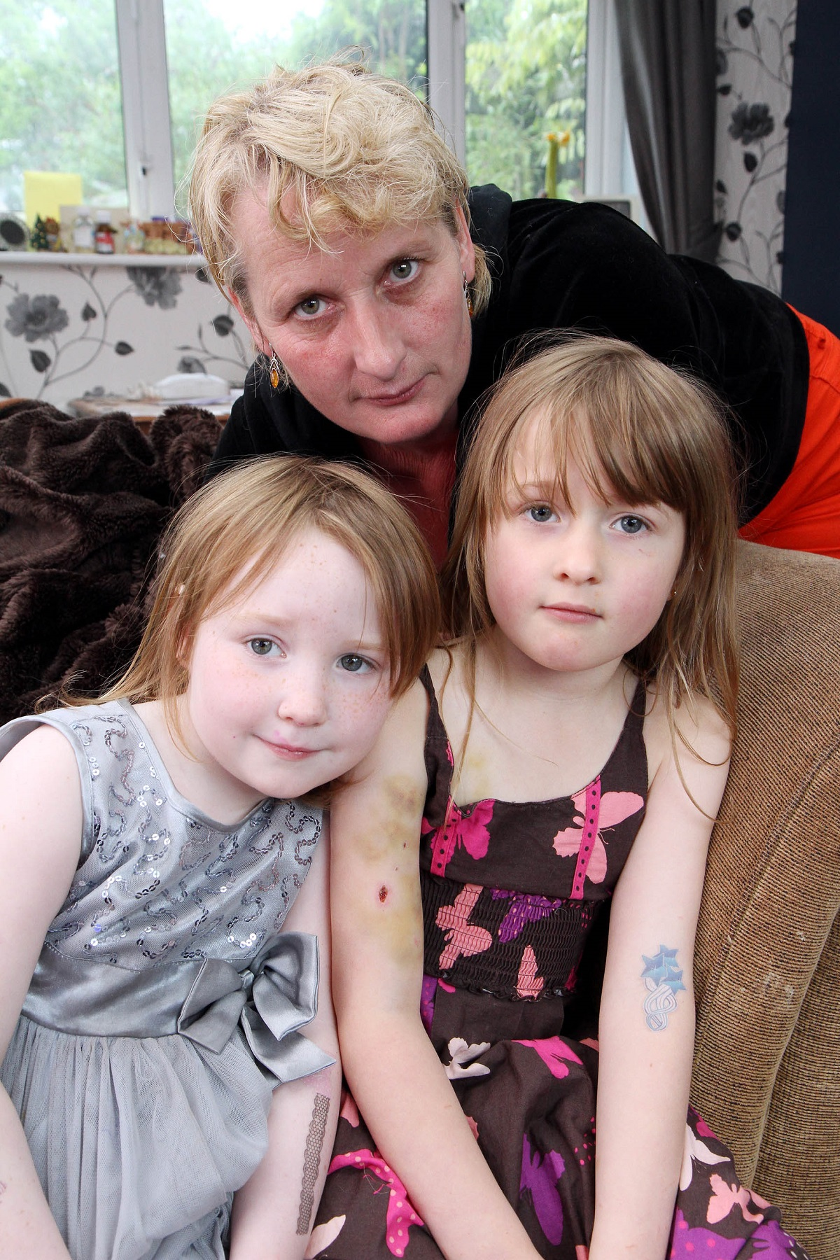 Grandma Lisa Reynoldson with Molly Watt, four, left, and her sister Evie Rockcliffe, six, who were attacked by a dog