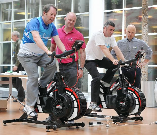 Director of FitBack Physiotherapy, Jonathan Daniel, and Nuffield Health's Andrew Nichols check on the progress of cyclists Martyn Jones, from Morrisons, and Robert Manson from Sue Ryder, at the cycle event