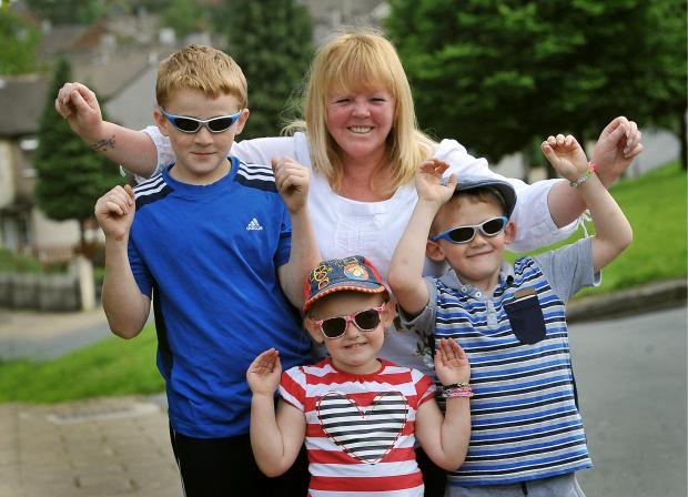 Bradford Telegraph and Argus: Karen Wright and her grandchildren Lewis Mitchell, Harvey Bendig and Emily Bendig, celebrate the news that their passports can be collected
