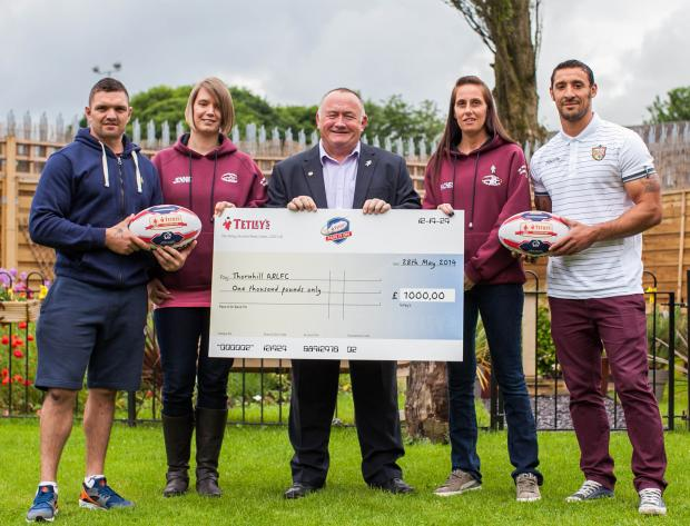 Thornhill Trojans receive their £1,000 cheque from Tetley's' Pass It On campaign by Super League players Danny Brough, left, and Paul Sykes, right (6950835)