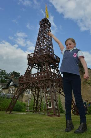 TRES BIEN! Charlotte Collinson, seven, pretends to touch the top of the Eiffel Tower replica in Burley-in-Wharfedale