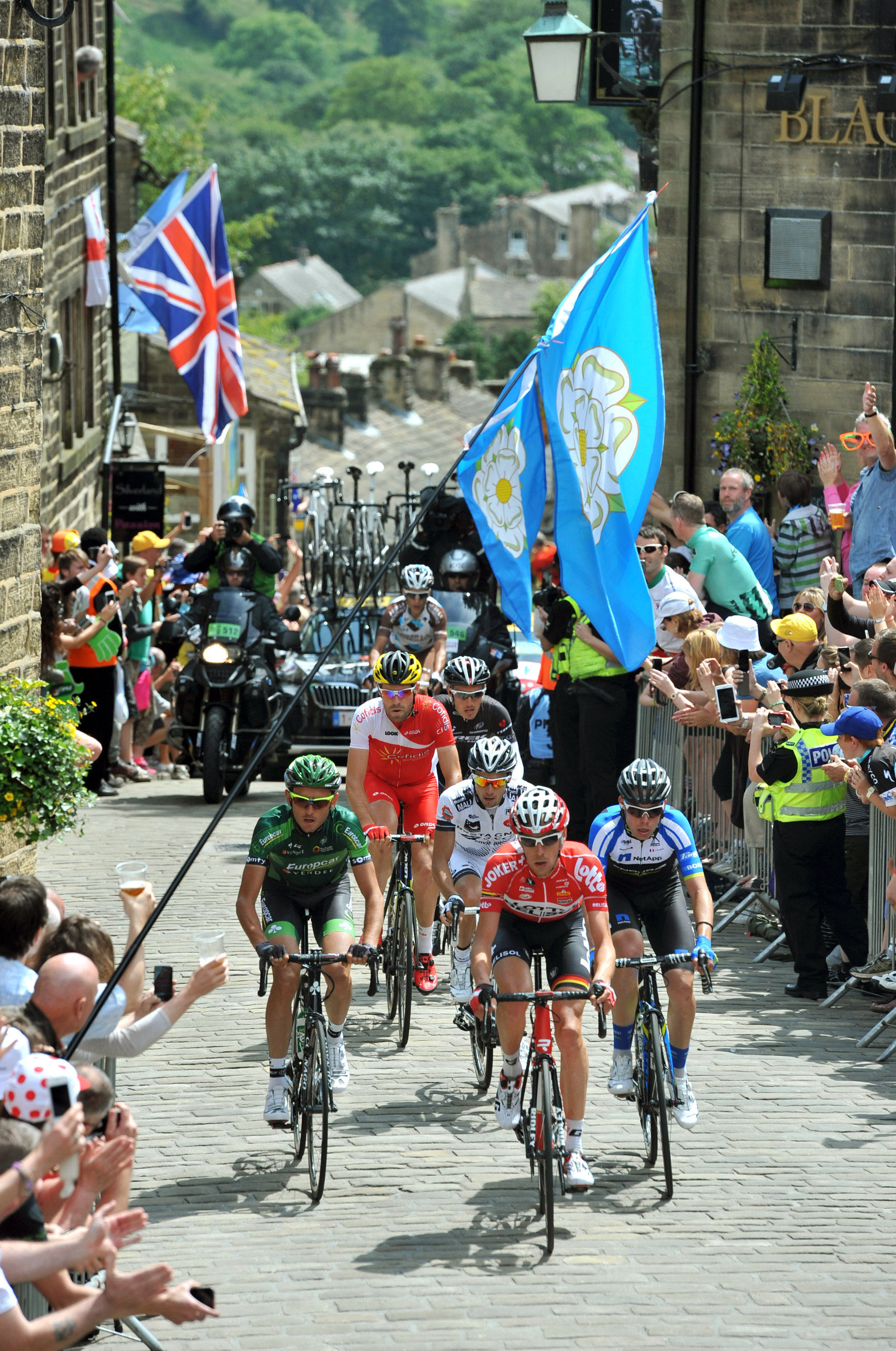 Crowds line Main Street, Haworth, to watch the riders tackle the cobbled climb