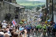 ALL SMILES: Spectators watch the peloton ride up Main Street in Haworth as Yorkshire embraces the Tour de France