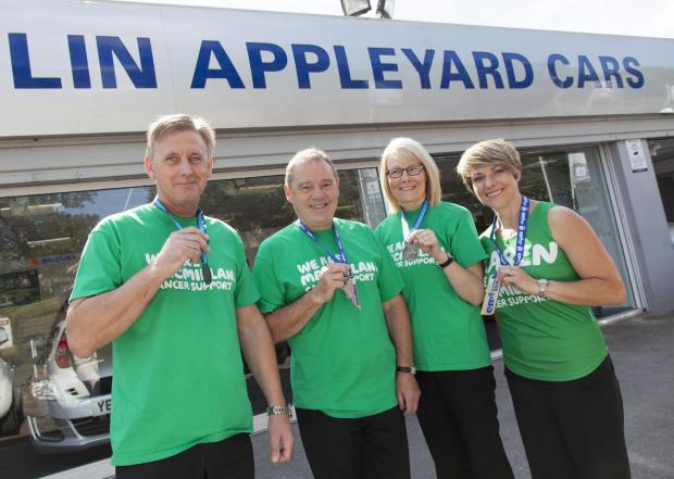 Four members of the Colin Appleyard fundraising team with their event medals, from left, John Appleyard, Tony Moyle, Judith Parker and Karen Halifax