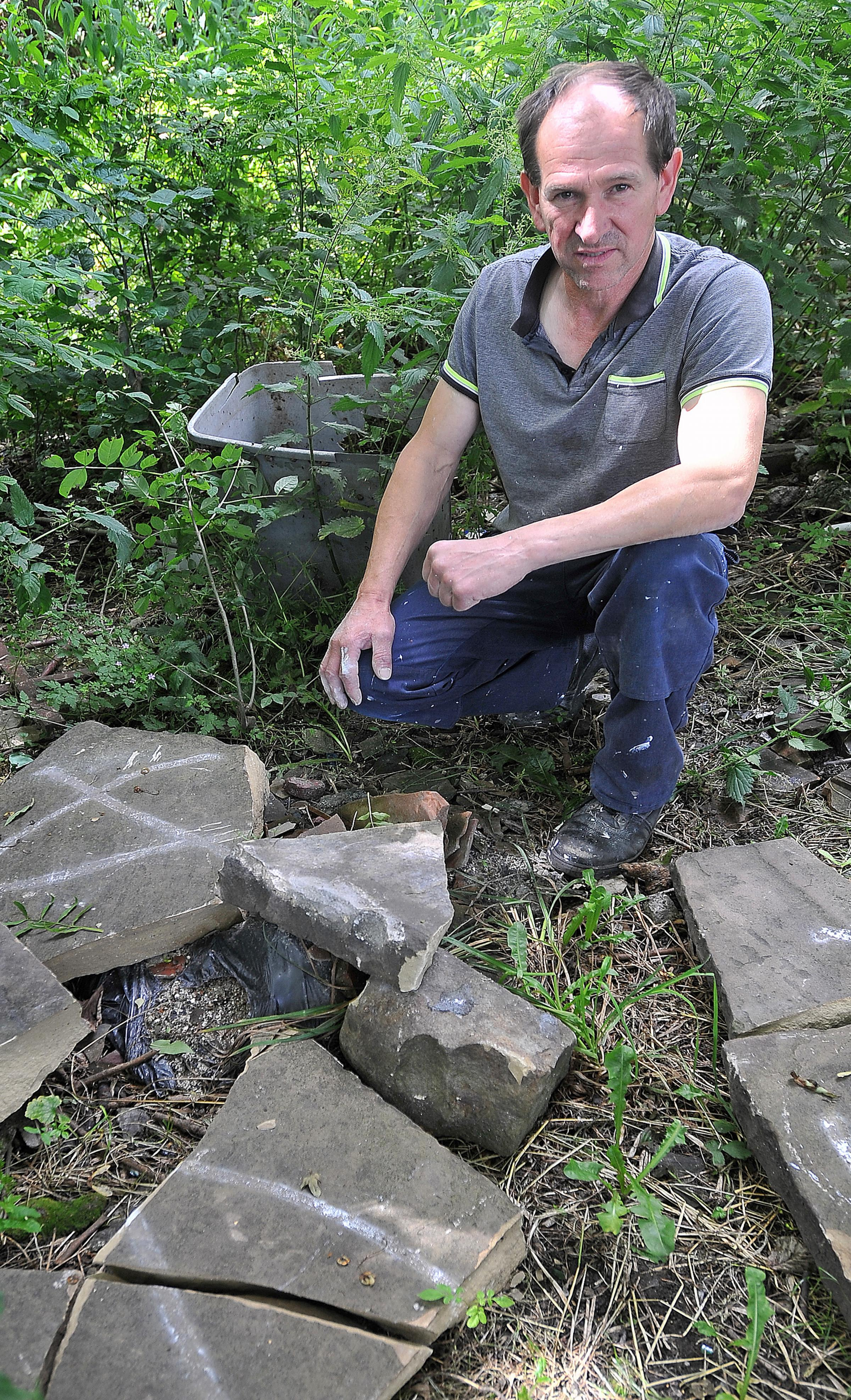 APPEAL: Roofer Misha Kozlow with some of the broken flag stones thieves have left behind