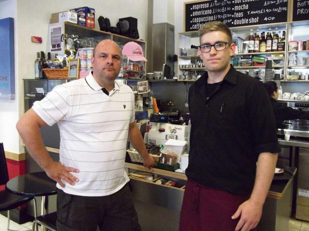 SICKENED:  Stuart Tolch, (left), with La Stazione manager Max Crane at the counter where the charity box was stolen