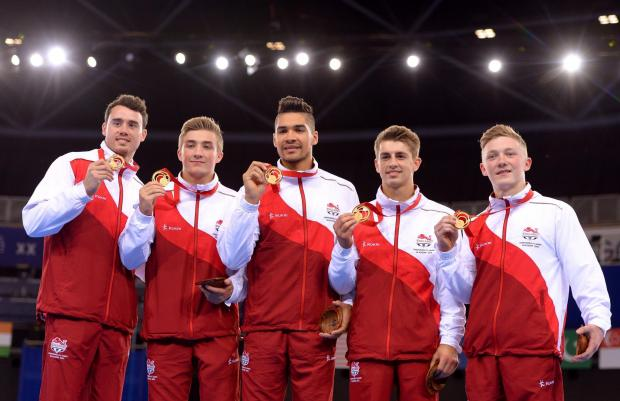 Nile Wilson, right, shows off his gold medal with his England gymastics team-mates