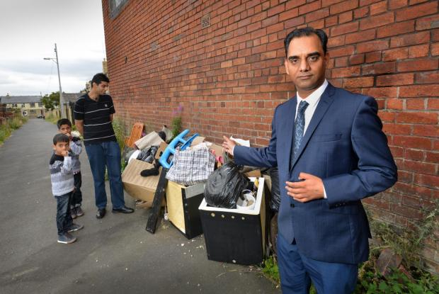 ANNOYED: Councillor Mohammed Shafiq, front, with residents frustrated at the fly-tipping on Redmire Street in Bradford Moor