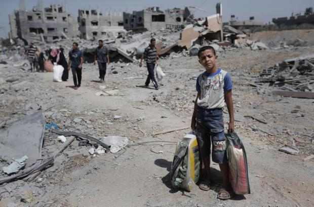 Palestinians carry their belongings after salvaging them from their destroyed house in the heavily bombed town of Beit Hanoun, Gaza Strip