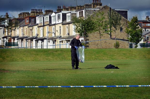 PROBE: An officer examines the scene where the man was found on fire
