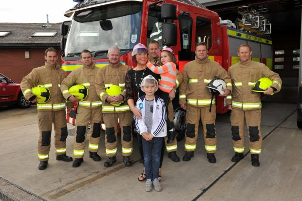 Firefighters from Cookridge with Kelly Laws and her daughter Maddie, who suffers from the rare genetic condition Rett Syndrome, and son George.