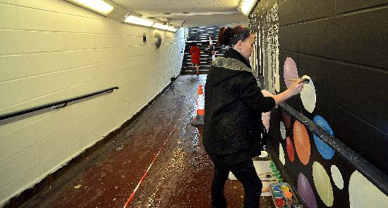 Lynn Smith painting a mural in a subway at Jacob's Well, Bradford