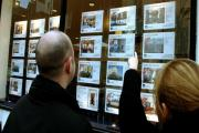 A young couple view properties through an estate agent's window