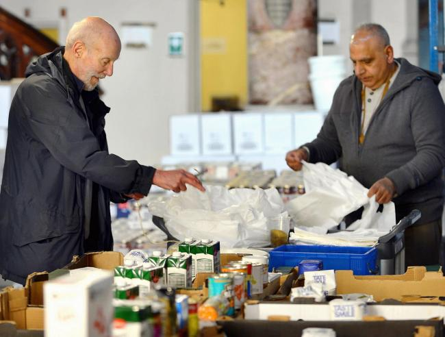 Keith Thomson and Lashman Singh packing food bags at St Mary's  Church, Barkerend so that food banks are able to feed the hungry people of their community