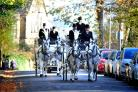 The funeral cortège headed by horse-drawn carriages makes its way to Scholemoor Crematorium