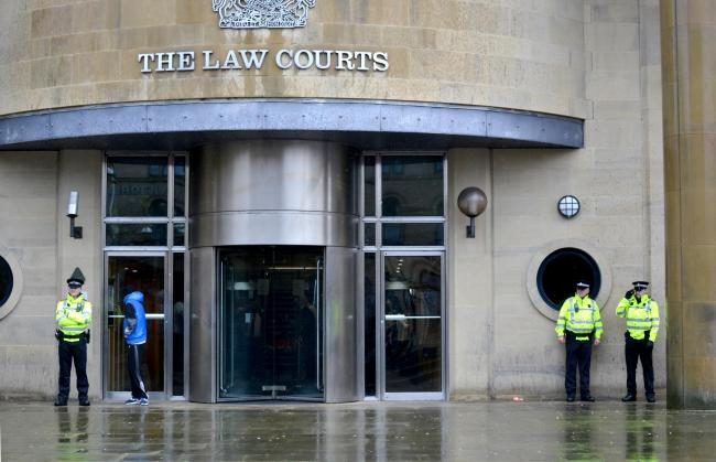 Police guard the entrance to Bradford Crown Court this morning