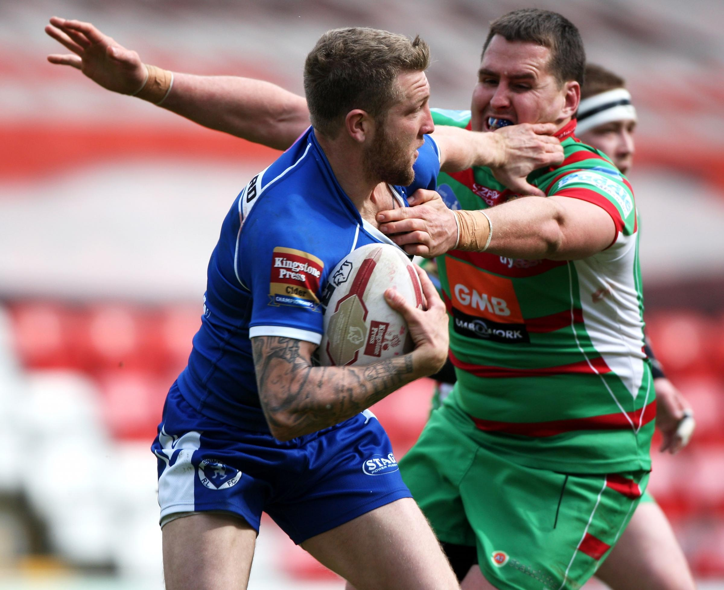 Ritchie Hawkyard fends off Brendon Rawlins during a Challenge Cup tie between Swinton and Cougars in 2014 at the Leigh Sports Village