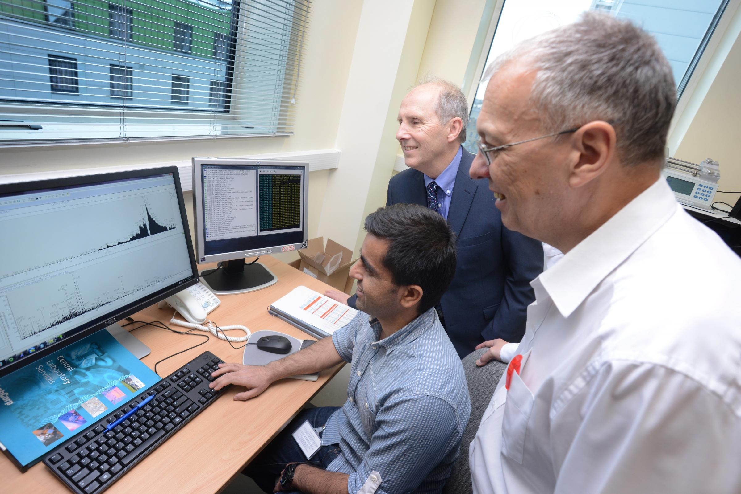 Newly-appointed research technician Sadr Ul Shaheed analyses data from the mass spectrometer machine alongside Professor Laurence Patterson and Dr Chris Sutton at the Institute of Cancer Therapeutics at the University of Bradford