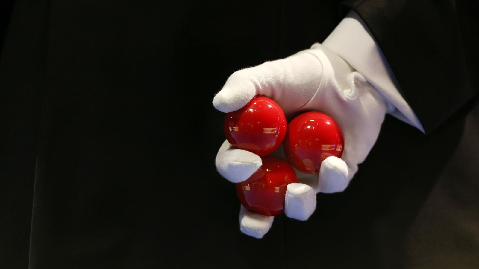 A snooker referee holds three red balls