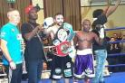 BELTING ACHIEVEMENT: Tasif Khan celebrates with both titles alongside beaten opponent Isaac Quaye