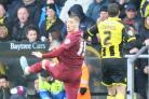 HIGH HOPES: Jamie Proctor wins a headed duel with Burton defender Phil Edwards