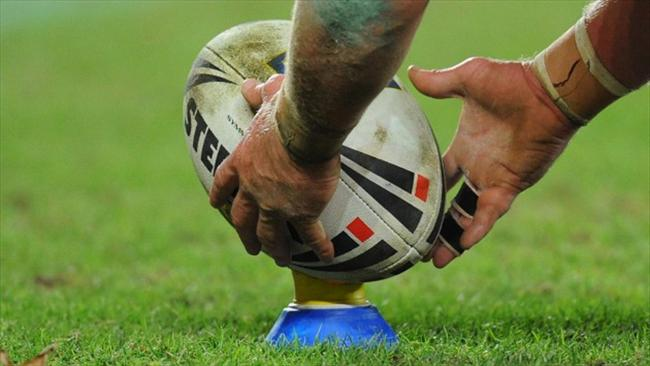 Man places rugby league ball on the kicking tee