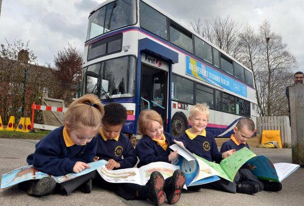 Bradford Telegraph and Argus: From left, Farfield Primary School pupils Ebony Digman, Ruben Kaai, Kassie Dean, Jack Gallagher and Joshua Bentley read outside the school's new library, an old First bus