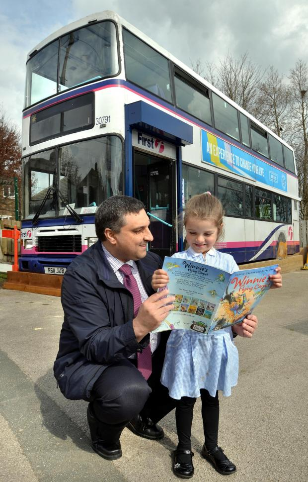 Bradford Telegraph and Argus: From left, Mohammed Raja, staff manager from First bus, helps pupil Lilenna Wormersley with her reading at Farfield Primary School