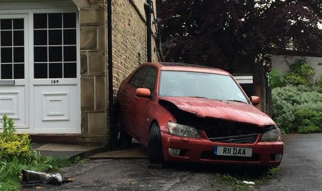 BIZARRE: An engine fault caused a car to reverse itself up a driveway and crash into its owner's house