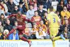 ON THE BALL: Kyel Reid takes on Millwall defender Joe Martin at Valley Parade in May