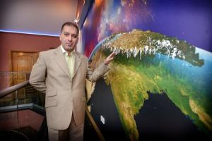 Haroon Rashid, the honorary ambassador for Gilgit-Baltistan in the UK, stands in front of a map showing the mountainous region claiming to be the rooftop of the world