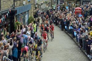 Riders taking part in the Tour de Yorkshire make their way up the cobbled streets of Haworth.