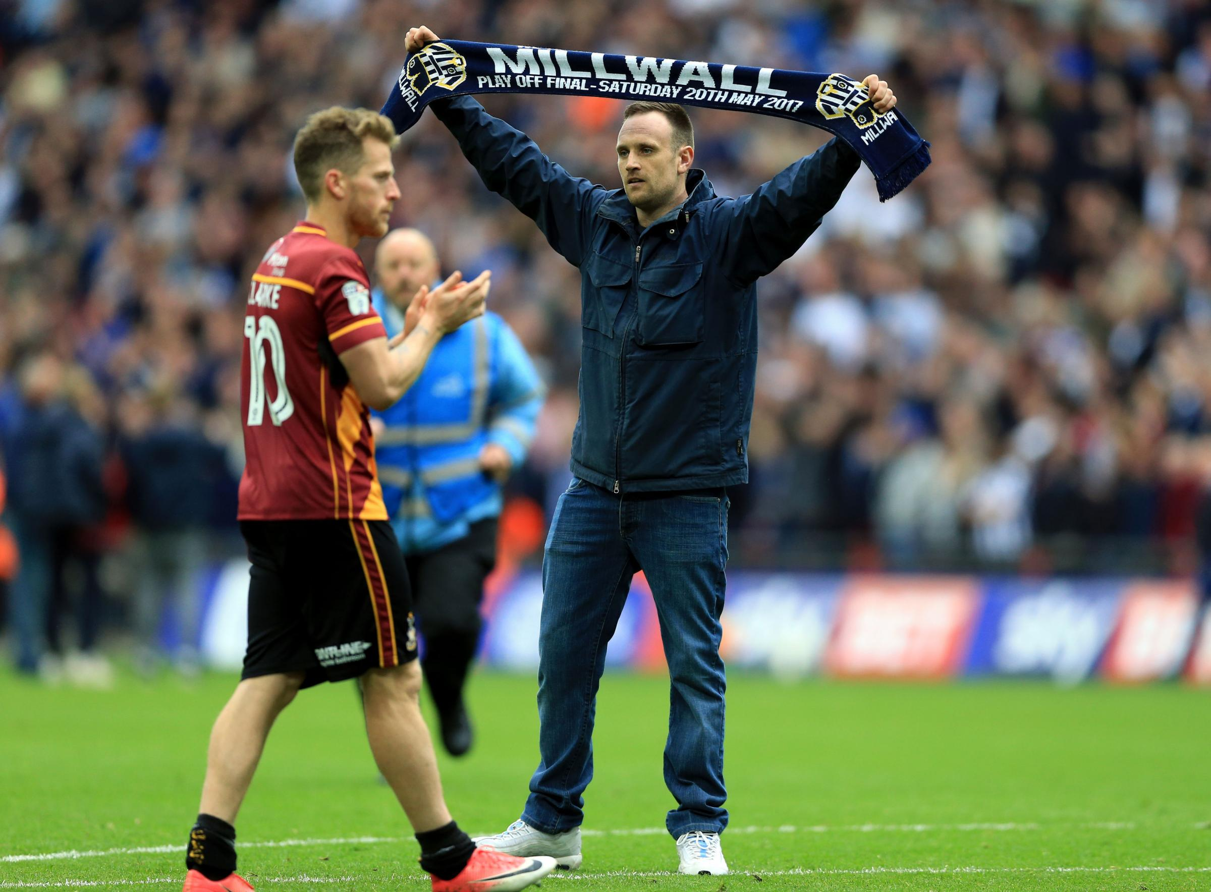 Bradford City's Billy Clarke confronted by a Millwall fans on the pitch after the League One play-off final at Wembley