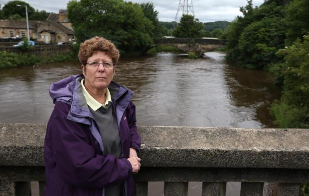 Bradford Telegraph and Argus: Cllr Jeanette Sunderland pictured by the River Aire at Apperley Bridge. A report into how to prevent future flooding is being scrutinised.  Picture: CHRIS BOOTH
