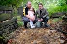 Churchwarden Adam O'Neil, his two-year-old daughter Holly and the Reverend Brunel James at the path where stone flags were stolen at Whitechapel Church in Cleckheaton
