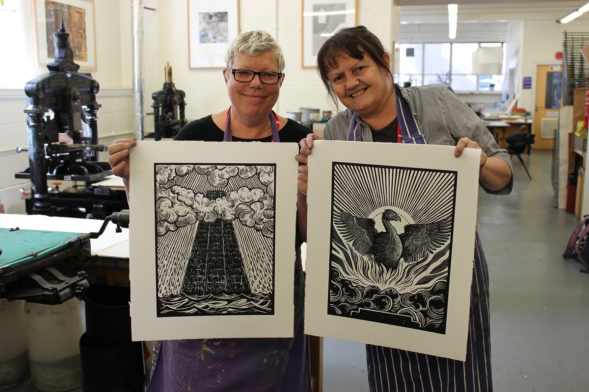 Caroline Hick (pictured holding the tower print) and artist Beth Smith (holding the Phoenix)