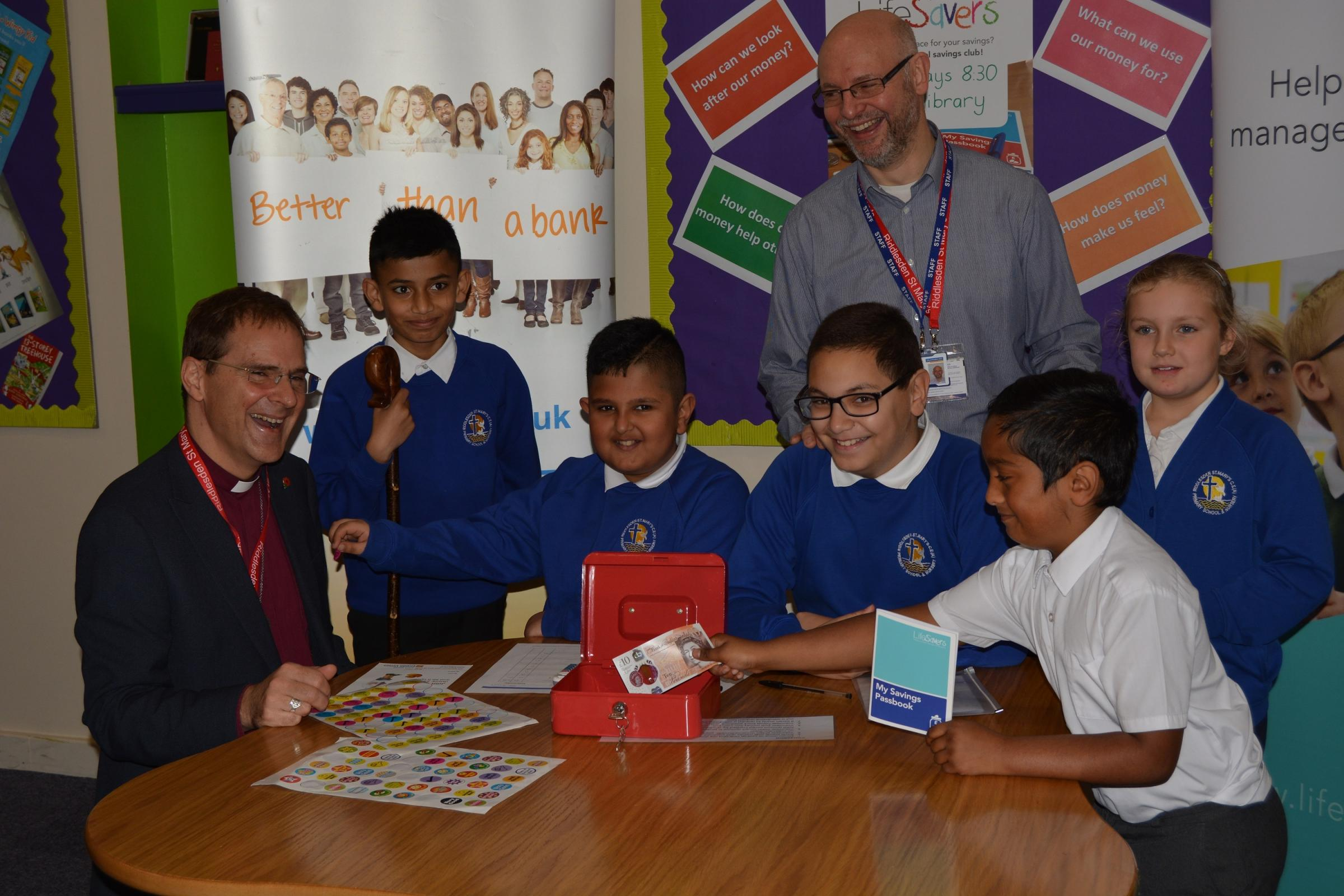 Bishop of Bradford, the Rt Rev Dr Toby Howarth, seated left, and Ian Brewer, the financial inclusion officer for the Bradford District Credit Union, standing centre, with pupils in the savings club at Riddlesden St Mary's Primary School.