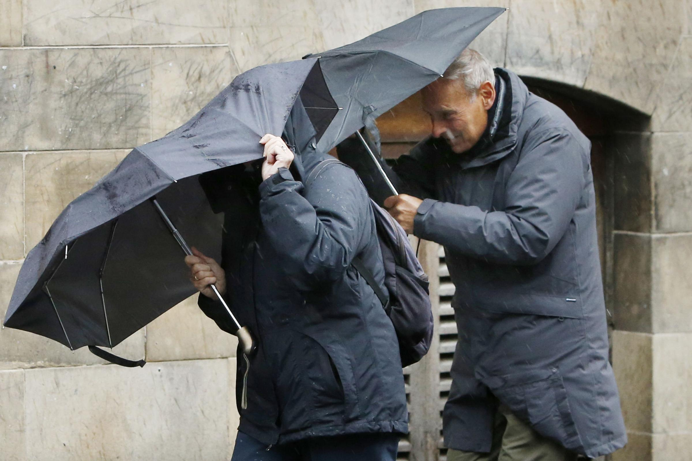 People with an umbrellas in the wind. Photo credit should read: Danny Lawson/PA Wire