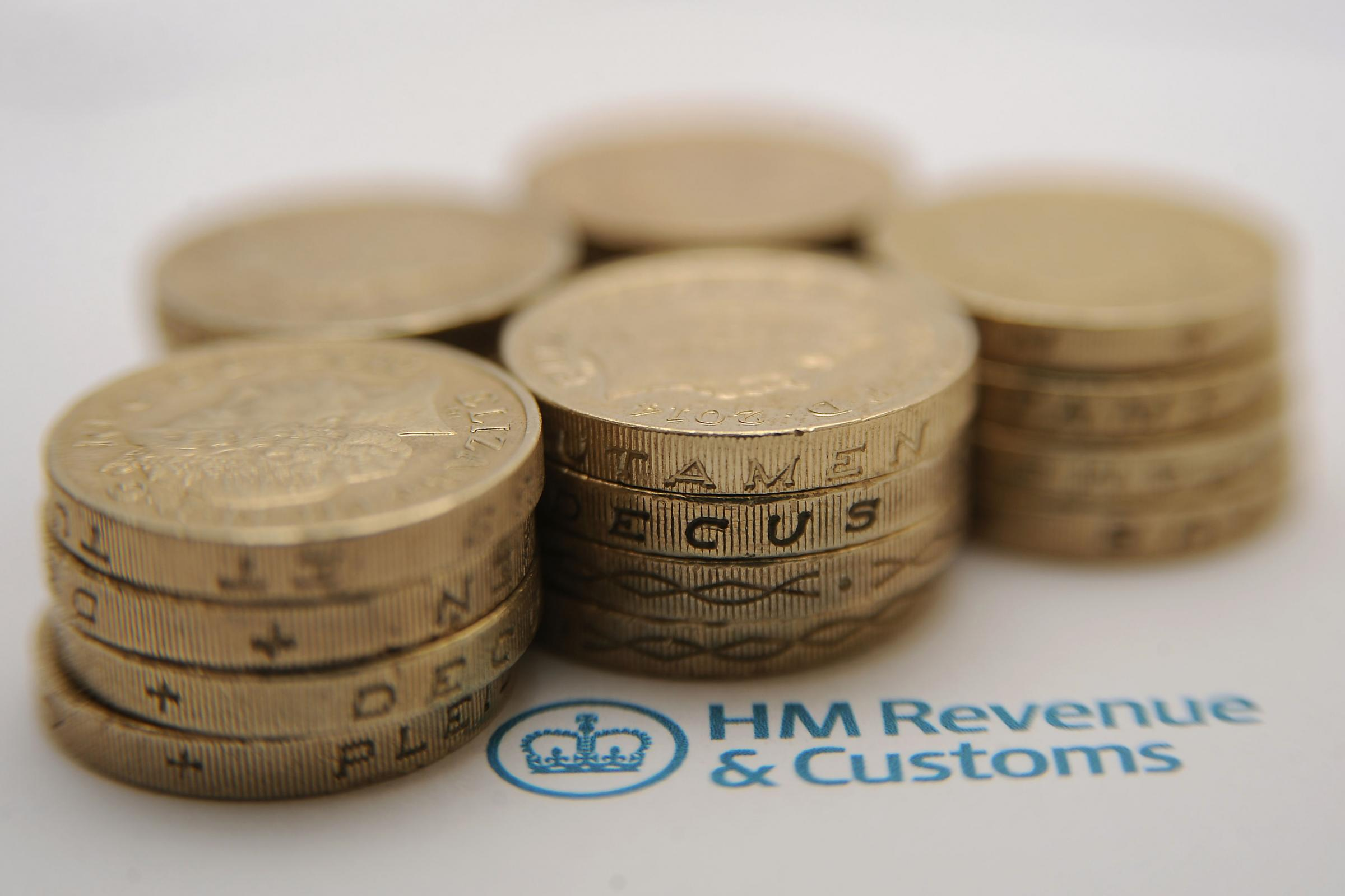 File photo dated 27/01/15 of pound coins next to the HM Revenue & Customs logo, as HMRC is planning to close 137 offices under a modernisation programme. PRESS ASSOCIATION Photo. Issue date: Thursday November 12, 2015. A total of 13 new regional centr