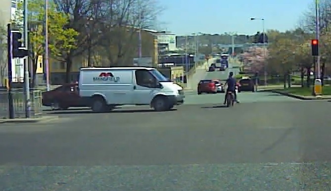The motorbike narrowly avoids a collision with a van and car