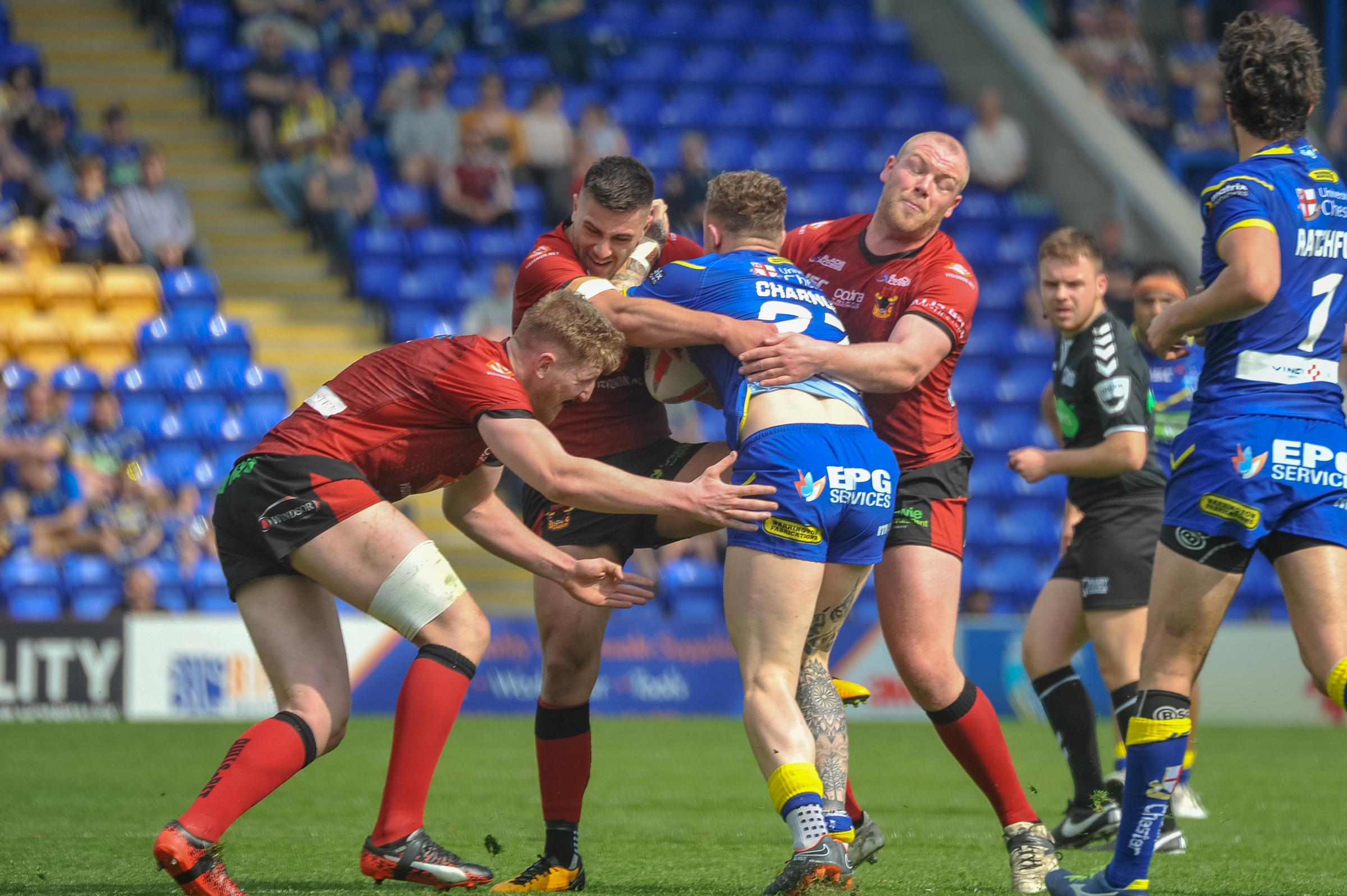 Steve Crossley, right, leads a three-man Bulls attempt to stop Warrington star man Josh Charnley